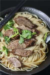 a bowl of noodles with beef sliced, garnish with coriander